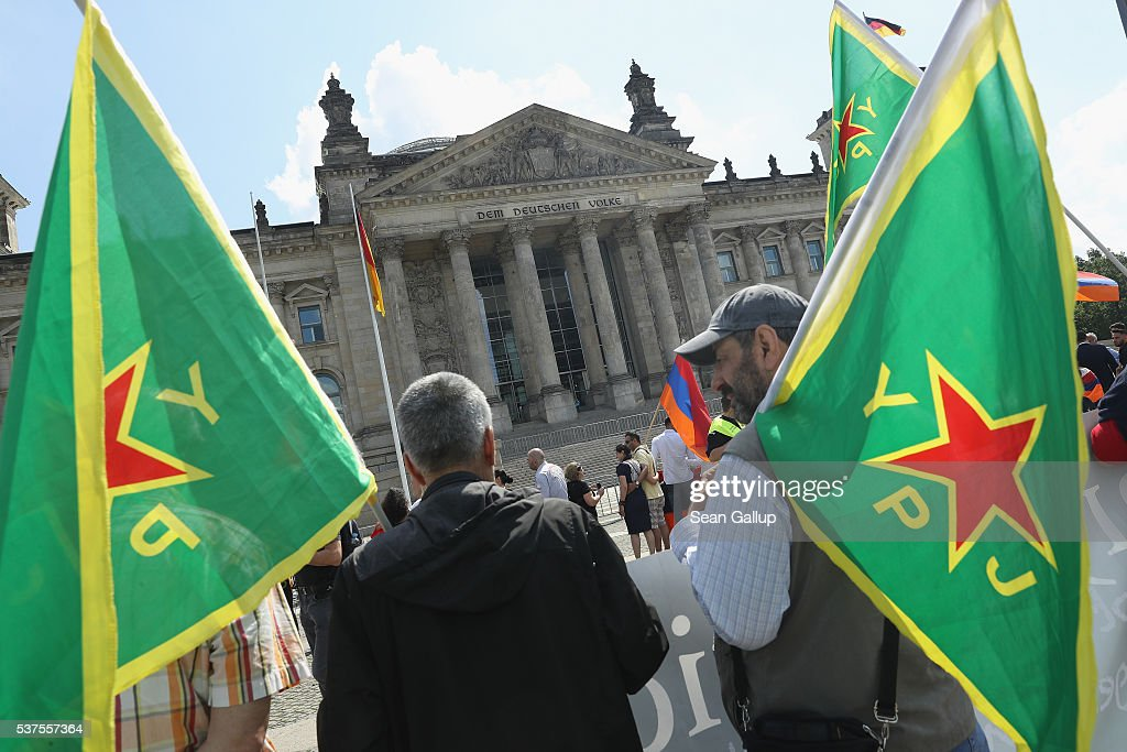 Two men carrying flags of the Kurdish YPG militias join a gathering to demand the recognition of the Armenian genocide outside the Reichstag, where the Bundestag was scheduled to vote on a resolution on the matter, on June 2, 2016 in Berlin, Germany. The Bundestag is likely to approve a resolution recognizing the 1915 deaths of hundreds of thousands of Armenians and other ethnic groups at the hands of Ottoman Turkish forces. The Turkish government has opposed any labeling of the deaths as genocide and an approval will likely irritate German-Turkish relations.