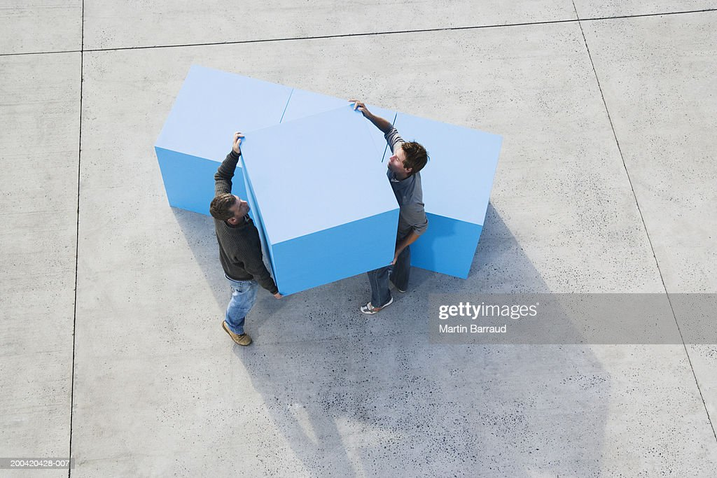 Two men carrying large blue block, elevated view : Stock Photo