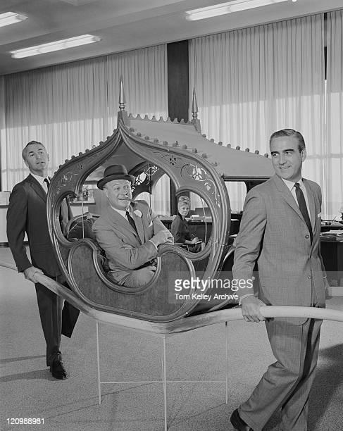 Two men carrying man on sedan chair