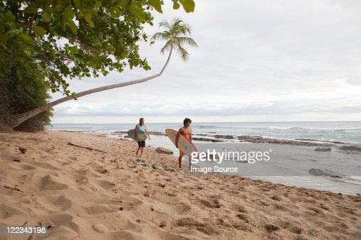 Two men carrying surfboards on beach : Stock Photo