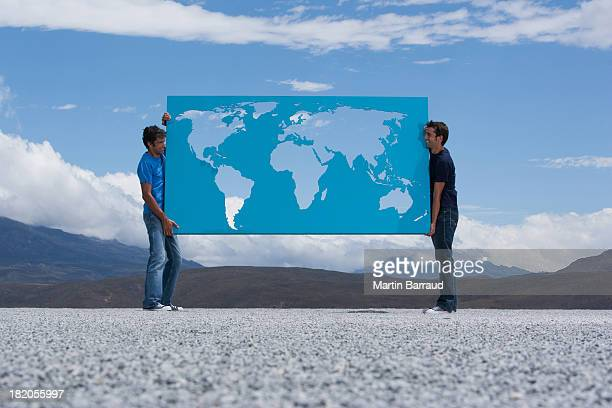 Two men carrying world map outdoors