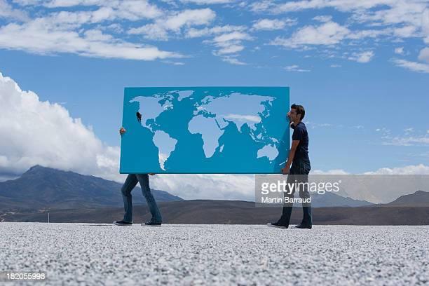 Zwei Männer tragen Weltkarte im Freien