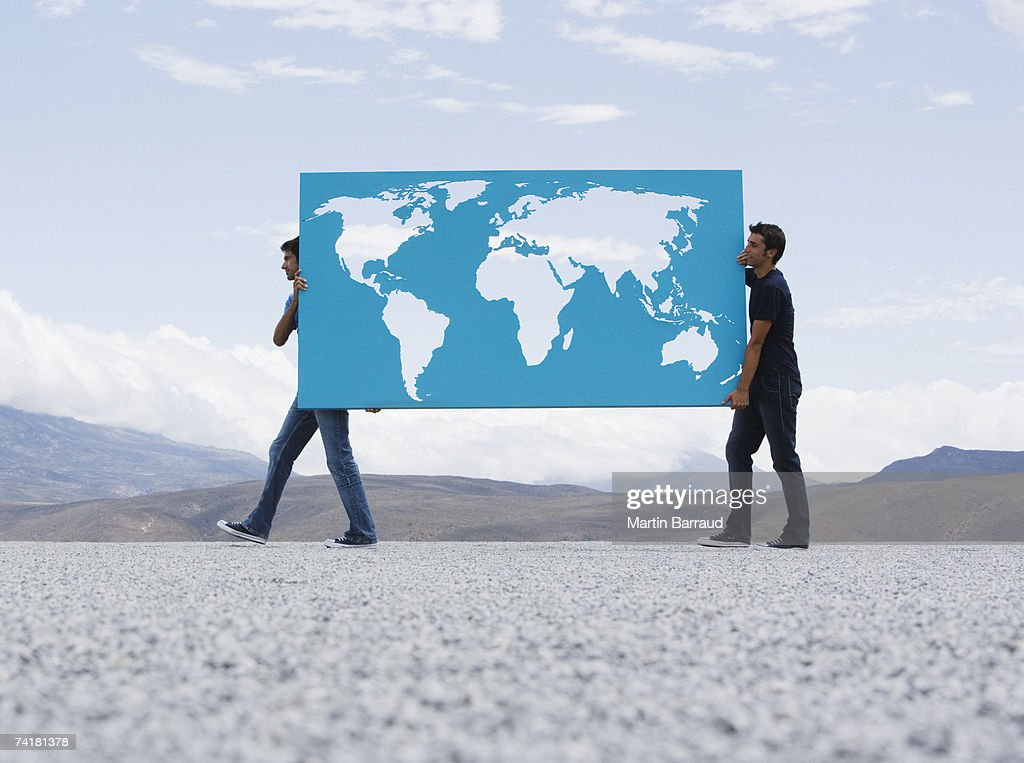 Two men carrying world map outdoors : Stock Photo