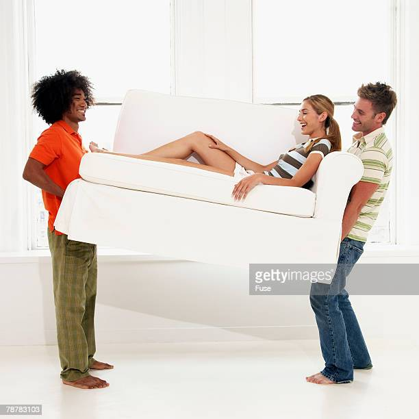 Two Men Carrying Young Woman on Sofa