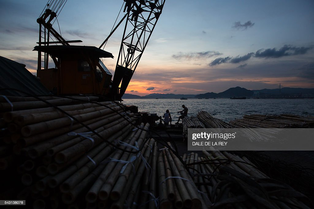 Two men chat behind piles of bamboo as the the sun sets over Victoria Harbour in Hong Kong on June 26, 2016. The official Hong Kong Observatory issued a hot weather warning on June 26 as a subtropical ridge continued to bring very hot weather to southern China. / AFP / DALE