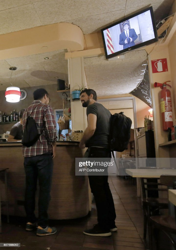 Two men chat in a bar as a television set broadcasts an institutional statement delivered by Catalan president Carles Puigdemont in Barcelona on October 4, 2017. Catalonia could declare independence on October 9, a regional government source told AFP, as a crisis escalates between Madrid and separatist leaders over an illegal independence referendum. /