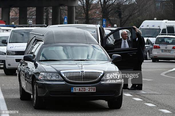 Two men chat next to a hearse parked outside Brussels Airport in Zaventem following twin blasts on March 22 2016 A series of apparently coordinated...