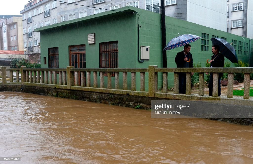 Two men chat next to an area flooded by the river Alvedosa in the village of Redondela, northwestern Spain, on February 13, 2016. / AFP / AFP or licensors / MIGUEL RIOPA