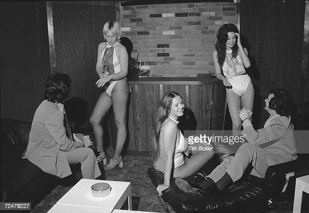 Two men chat with women in skimpy costumes in the reception room of a massage parlor early 1970s