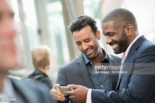 Two men checking a smart phone.