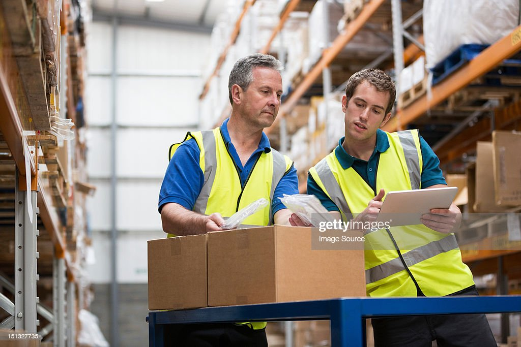 Two men checking stock in warehouse : Stock Photo