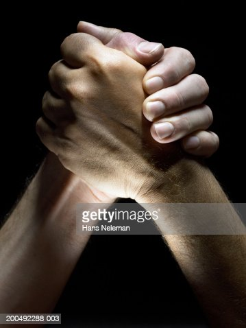 Two men clasping hands, close-up, side view : Stock Photo