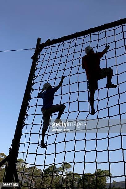 Two men climbing rope net