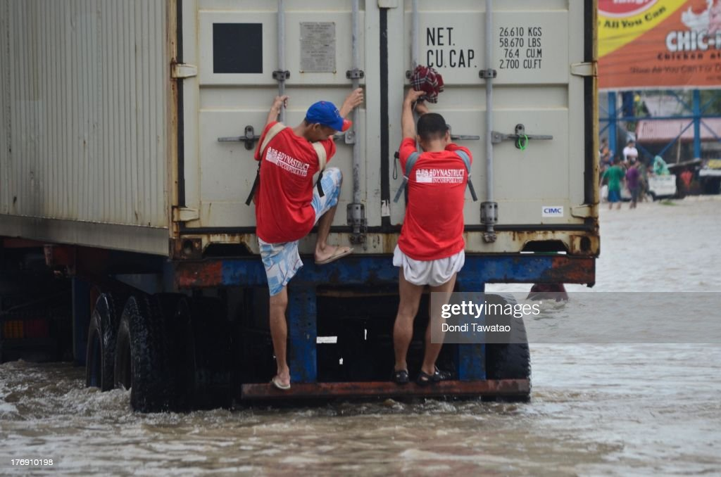 Two men cling on the back of a truck after floodwaters inundated parts of Las Pinas on August 19, 2013 in Las Pinas City south of Manila, Philippines. Tropical storm Trami which was enhanced by monsoon rains swept overnight through the southern metropolitan cities of Manila and leaving huge parts of four provinces underwater forcing residents to evacuate their homes and seek shelter in evacuation centers. At least three fatalities were recorded with thousands more still needing to be rescued.