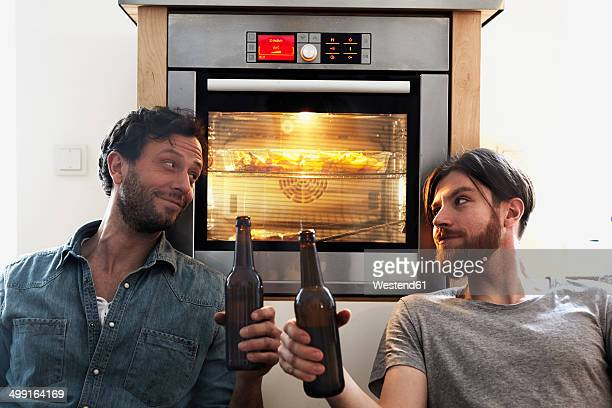 Two men clinking beer bottles at oven in kitchen