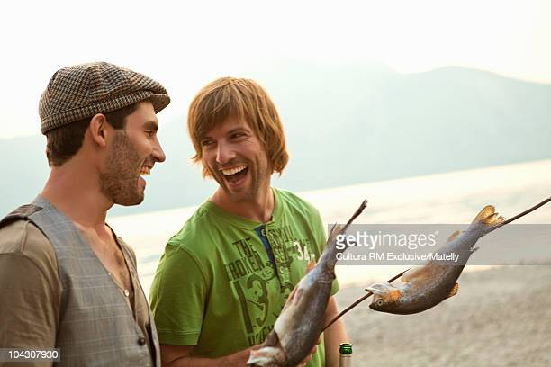 Two men comparing fish at a lake