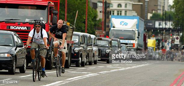 Two men cycle past a traffic jam during a 24hour Tube workers' stoppage on June 30 2004 in London England Members of the RMT walked out for a 24hour...