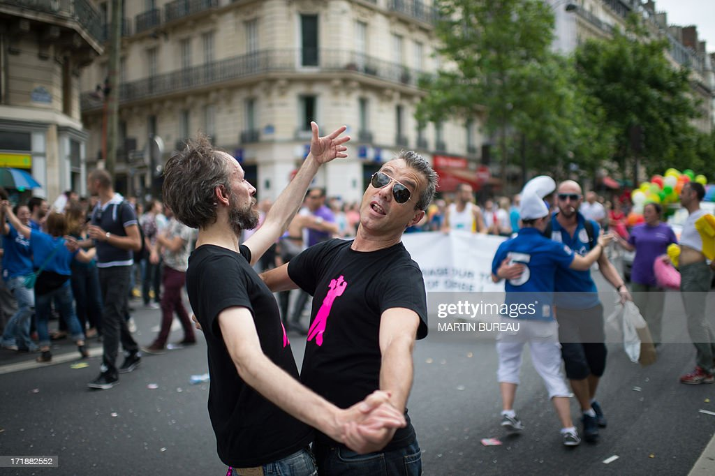 Two men dance together during the homosexual, lesbian, bisexual and transgender (HLBT) visibility march, the Gay Pride, on June 29, 2013 in Paris, exactly one month to the day since France celebrated its first gay marriage.