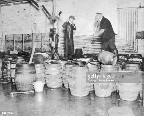 Two men destroy barrels of confiscated alcohol by taking axes to the contraband North Dakota 1929