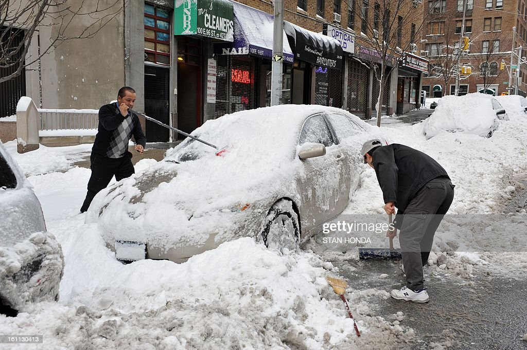 Two men dig out a car from an overnight snowstorm February 9, 2013 on East 96th Street in New York. AFP PHOTO/Stan HONDA