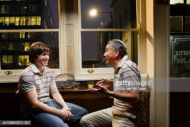 Two men discussing in bar, smiling