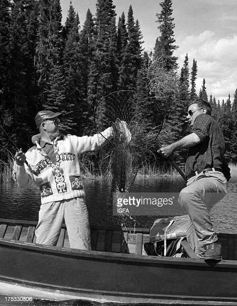 Two men display a northern pike in a fishing net in a small wooden boat in Canada circa 1960