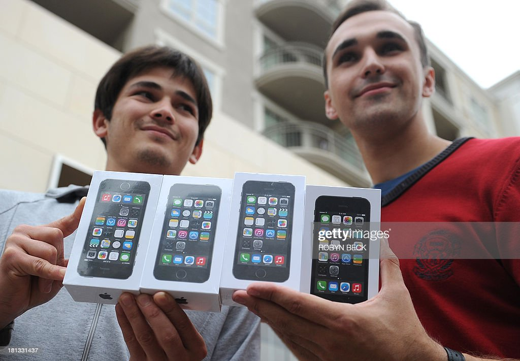 Two men display their four new iPhone 5S outside the Apple Store at the Americana at Brand shopping complex in Glendale, California, September 20, 2013. Apple launched two new models of the iPhone today - the iPhone 5S, which is an updated version of the iPhone 5, and a less expensive version, the iPhone 5C. AFP PHOTO / Robyn Beck