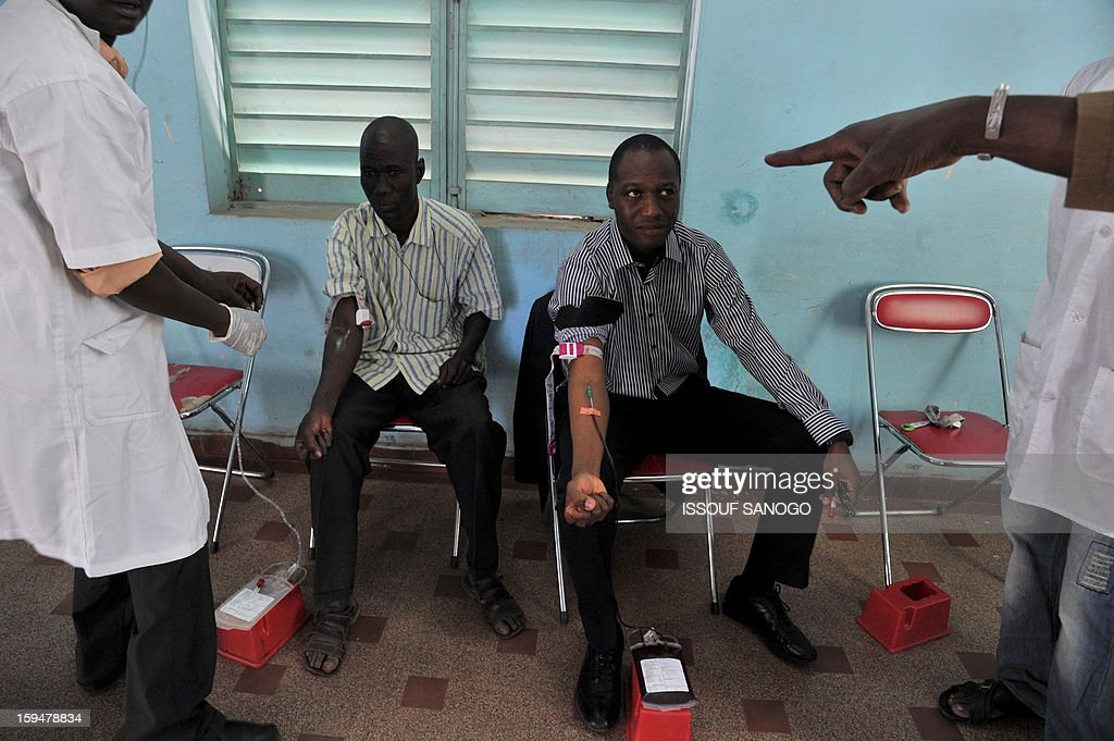 Two men donate blood for the injured, on January 14, 2013 in Bamako. Islamists have retreated in the east of Mali but French forces are facing a difficult situation in the west of the country where rebels are well armed, French Defence Minister Jean-Yves Le Drian said on January 14. France launched the operation alongside the Malian army on January 11, 2013 to counter a push south by the insurgents who had threatened to advance on the capital Bamako. AFP PHOTO / ISSOUF SANOG0
