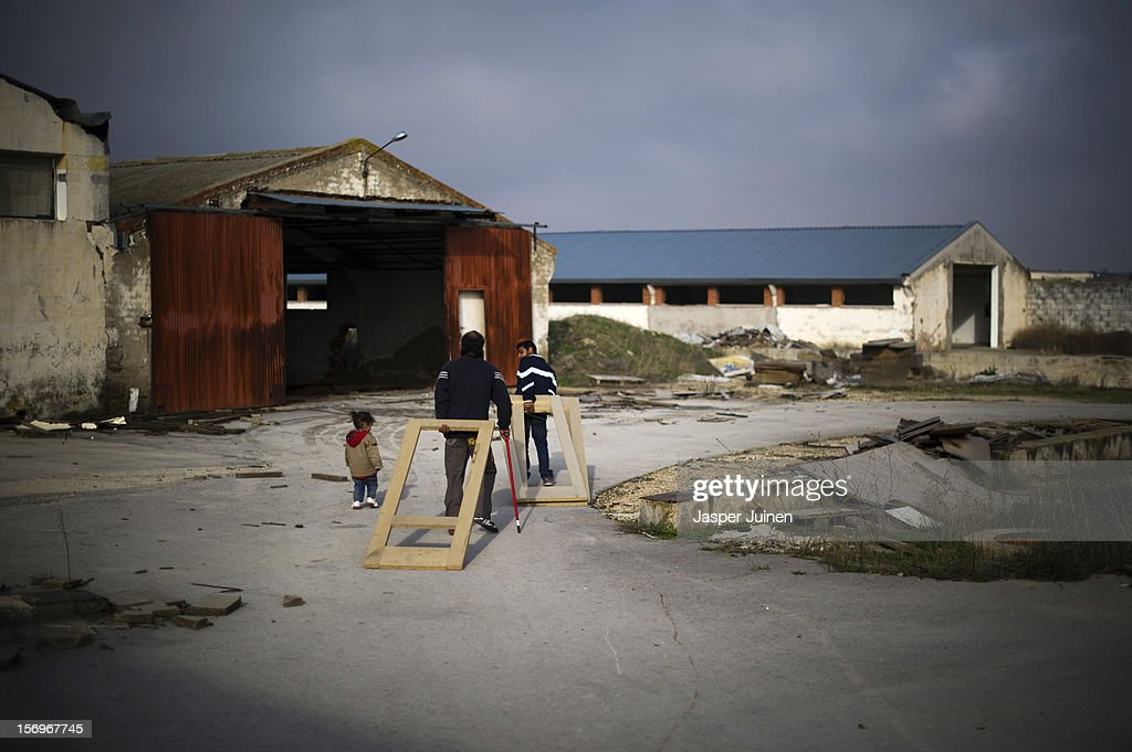 Two men drag unfinshed doors behind them, to be used as burning wood for their stoves at home, on the terrain of the abandoned Mavisa door factory on November 22, 2012 in Villacanas, Spain. During the boom years, where in its peak Spain built some 800,000 houses a year accompanied by the manufacturing of millions of wooden doors where needed, the people of Villacanas were part of Spain's middle class enjoying high wages and permanent jobs. During the construction boom years the majority of the doors used within these new developments were made in this small industrial town. Approximately seven million doors a year were once assembled here and the factory employed a workforce of almost 5700 people, but the town is now left almost desolate with the Villacanas industrial park now empty and redundant. With Spain in the grip of recession and the housing bubble burst, Villacanas is typical of many former buoyant industrial Spanish towns now struggling with huge unemployment problems.