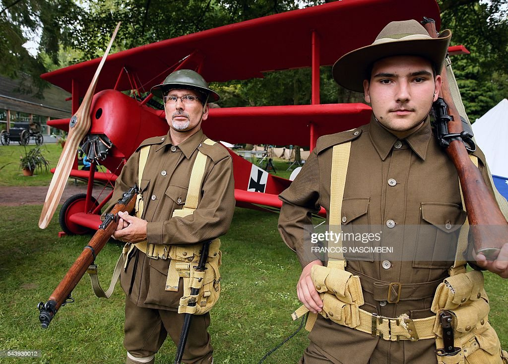 Two men dressed as Australian WWI French stand in front of a replica of the Fokker Dr.I, the fighter aircraft of German Manfred von Richthofen aka the Red Baron during a ceremony to commemorate the centenary of the battle of the Somme, one of the deadliest of the World War I (1.2 million killed, missing and wounded in five months), on June 30, 2016 in Albert, northern France. / AFP / FRANCOIS