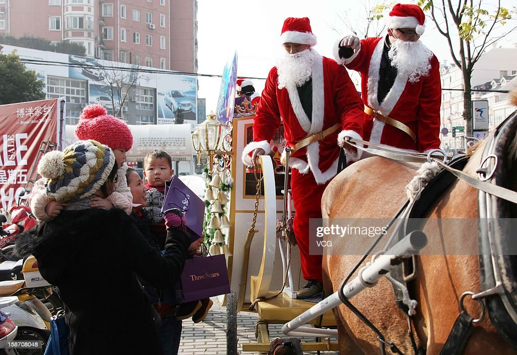 Two men dressed as Santa Claus drive a carriage to distribute gifts to children on December 24, 2012 in Haining, China. Though Christmas is not officially celebrated in China, the holiday is becoming increasingly popular as Chinese adopt more Western ideas and festivals.