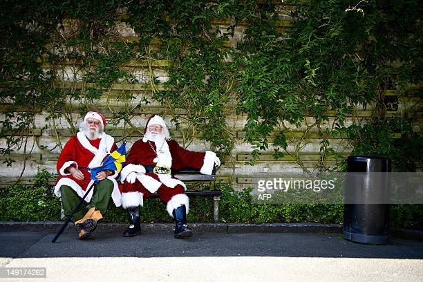 Two men dressed as Santa Claus rest on a bench on July 24 during a visit by the participants of the annual World Santa Claus Congress to the...
