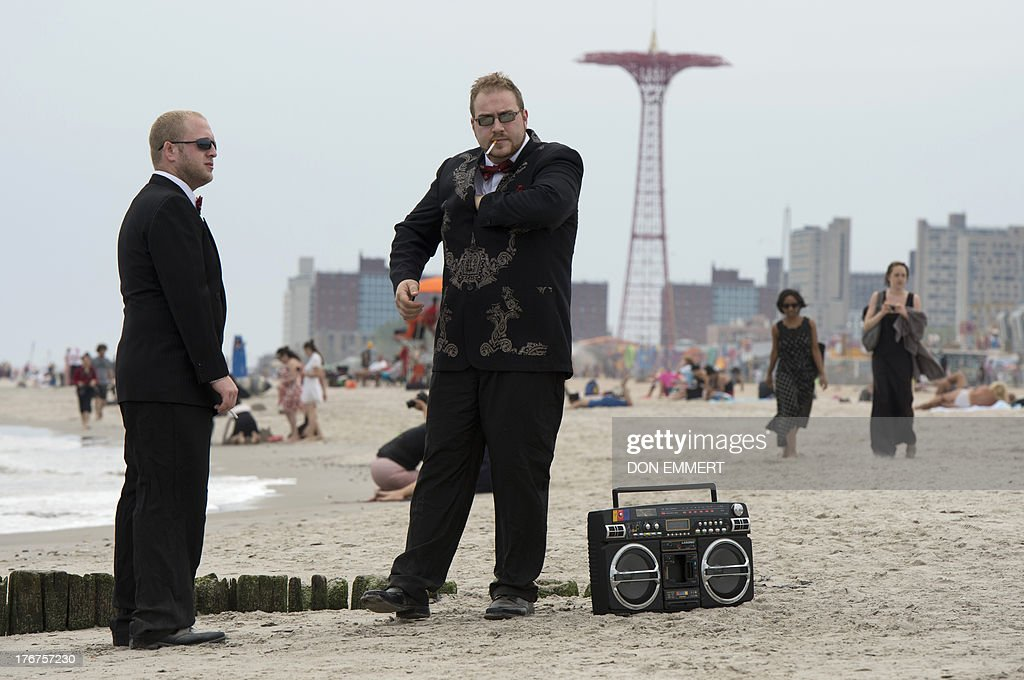 Two men dressed in black tie take a cigarette break as part of ImprovEverywhere.com's Black Tie Beach event August 18, 2013 in Coney Island, New York. Scores of men, women and children gathered for a day at the beach dressed in their Black Tie attire for the annual Black Tie Beach. AFP PHOTO/Don Emmert