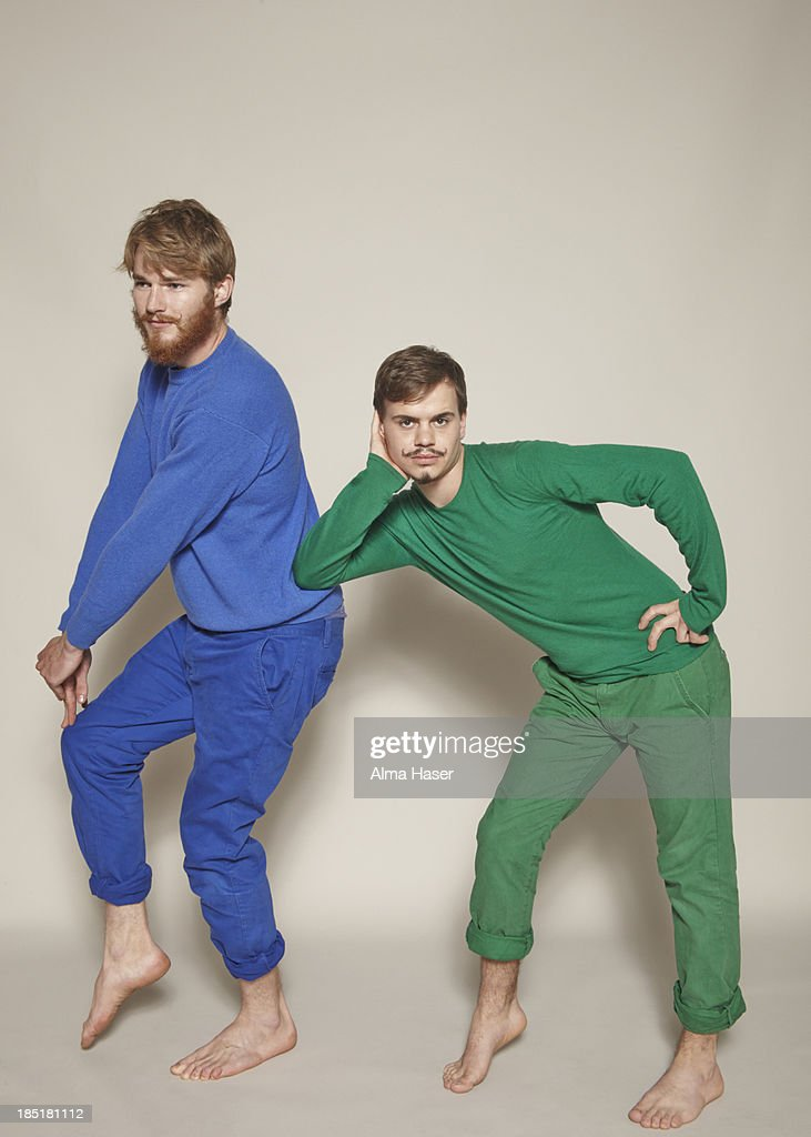 Two men dressed in blue and green posing : Stock Photo