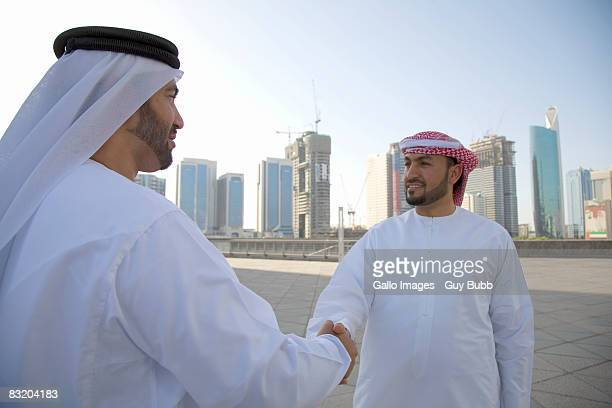 Two men dressed in traditional Middle Eastern attire greeting each other, Dubai cityscape in background, UAE