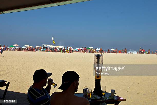Two men drink beer at the Copacabana beach in Rio de Janeiro Brazil on Saturday Aug 4 2013 Investors are betting on billionaire Jorge Paulo Lemann to...