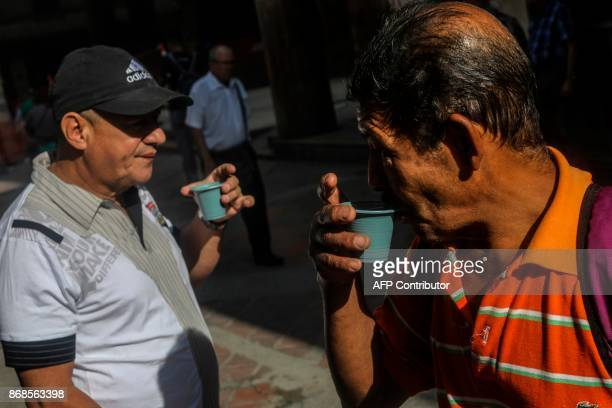 Two men drink coffee at the Berrio square in Medellin on October 30 2017 October is the peak of the high season coffee harvest in the region of...