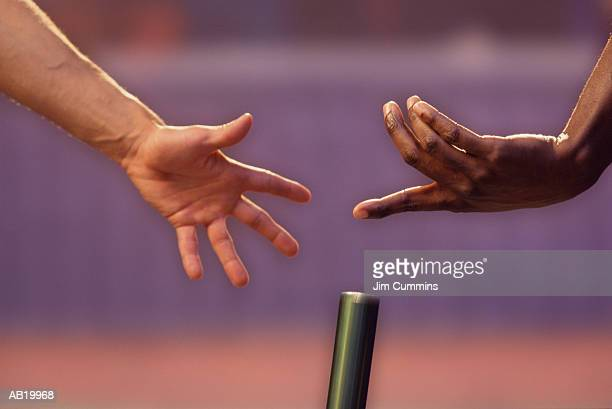 Two men dropping relay baton, focus on hands, close-up