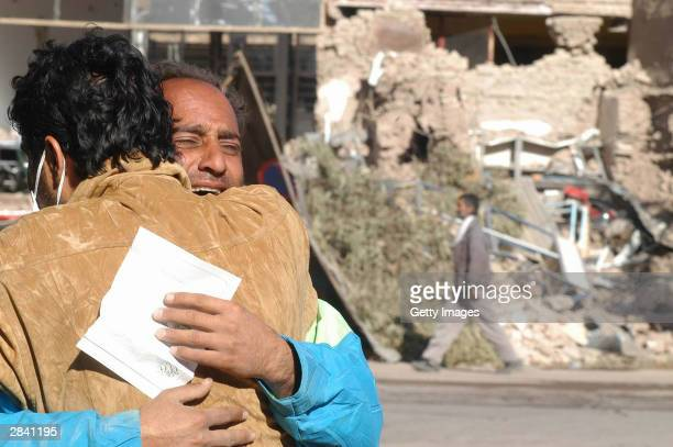 Two men embrace January 2 2003 in Bam Iran A week after a massive earthquake shattered Bam killing some 30000 people residents are digging out and...