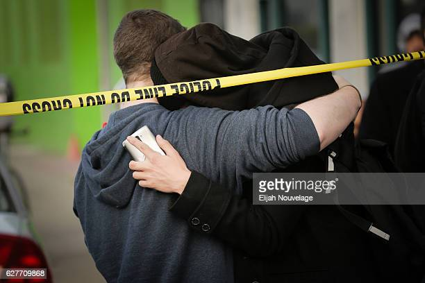Two men embrace near the site of a warehouse fire that has claimed the lives of at least thirtythree people on December 4 2016 in Oakland California...