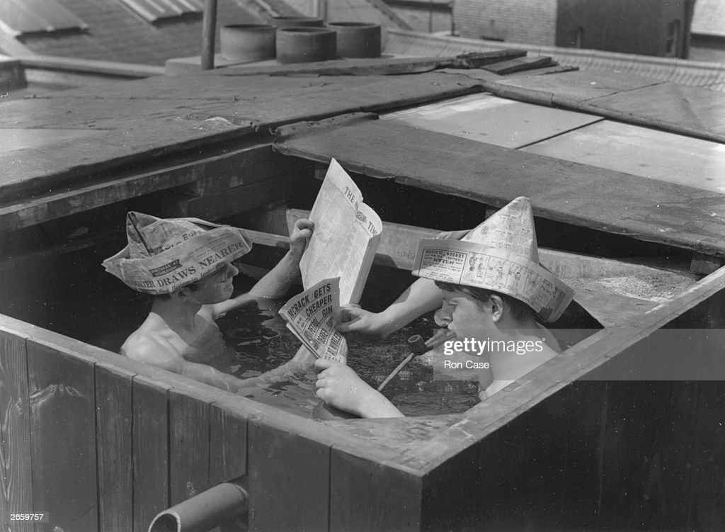 Two men enjoying the heatwave in a tub of water, using pages from their newspaper as sun hats.