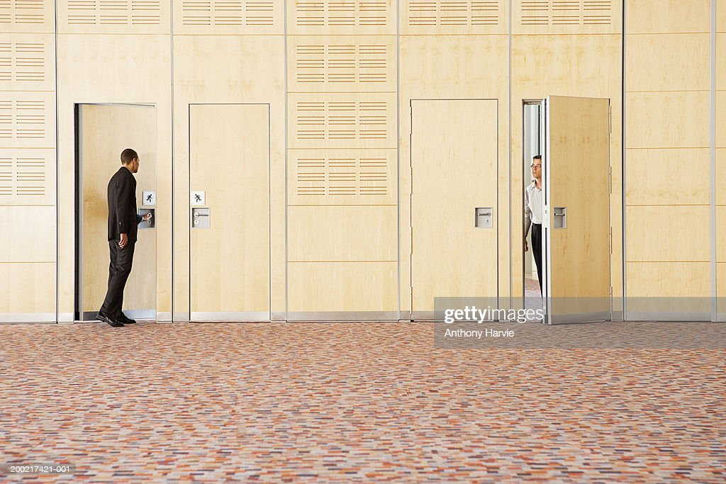 Two men entering and exiting empty room : Stock Photo