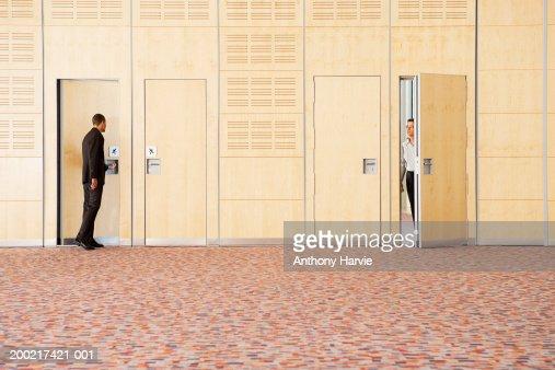 Two men entering and exiting empty room : Foto de stock