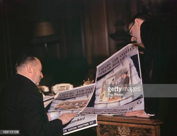 Two men examining British Ministry of Health wartime posters aimed at reducing absenteeism from war work circa 1942 The slogan reads 'Coughs and...