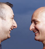 Two men face to face, laughing, profile, close-up