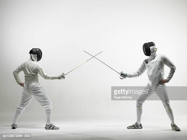 Two men facing off in fencing match, studio shot