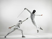 Two men fencing, studio shot