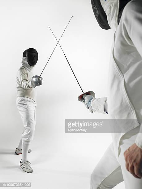 Two men fencing, studio shot