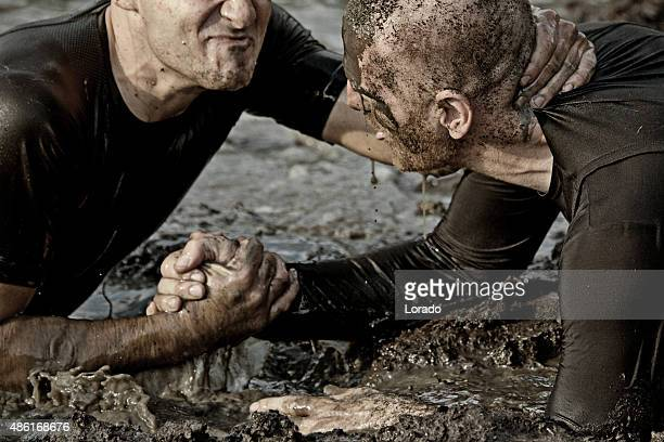 two men fighting in mud