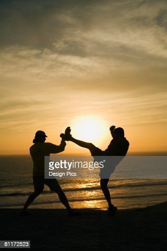 Two men fighting on a beach : Stock Photo